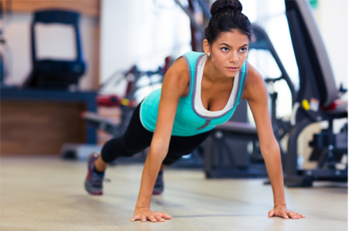 Sports woman doing push ups in fitness gym