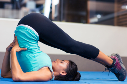 Portrait of a young woman doing yoga exercises in gym